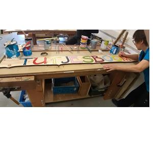 Opdrachten in het houtatelier: inschilderen van letters