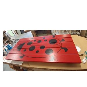 Producten van het houtatelier: beschilderd tafelblad van een tuinbank